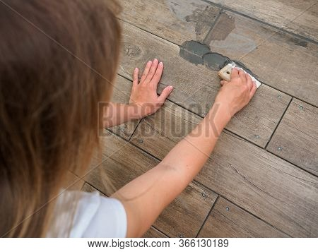 Grouting Between Ceramic Tiles. The Girl Works With A Spatula. Repair In The Room