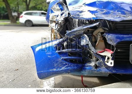 Close-up Of A Blue Totally Wrecked Car On A Street In A Parking Lot. Destroyed Bumper, Headlight, Ho