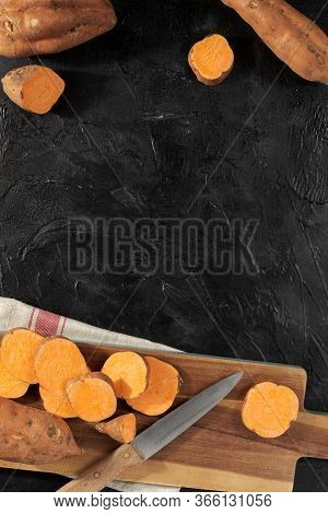 Raw Sweet Potatoes On Wooden Kitchen Board Top View.