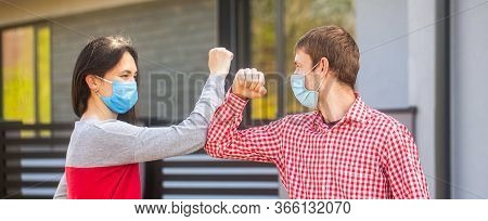 Couple Greeting With Elbows. Elbows Bump. Friends In Protective Medical Mask On His Face Greet Their