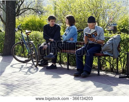 Voronezh, Russia - May 1, 2018: Visitors To The City Square Relax On A Bench. An Elderly Man Reads A