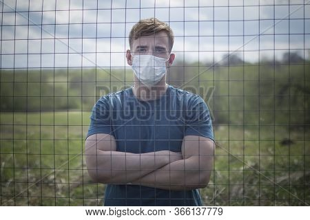 Guy Prisoner In Protective Mask On His Face Isolated Standing Behind Bars, Lattice. Restriction Of F