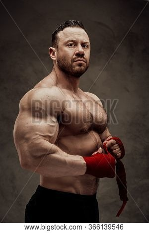 Handsome Adult Athlete Wearing Sportswear Posing For A Camera While Taping His Arms With Bandage In