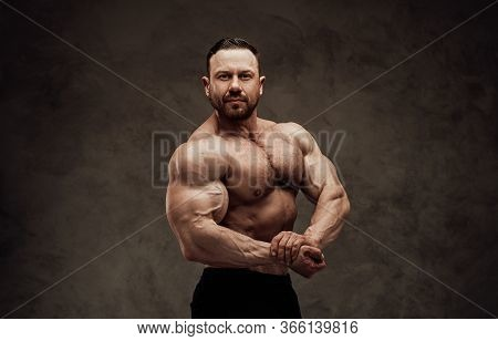 Motivated Strong Man Posing In The Dark Studio, Ready To Start A Workout And Showing His Big Biceps