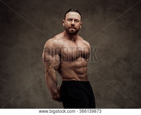 Focused And Energetic Fitness Trainer Looking Cheerful Showing His Abdominal And Triceps Muscles In