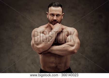 Shirtless Adult Male Bodybuilder Posing, Looking Thoughtful And Interested In A Dark Studio