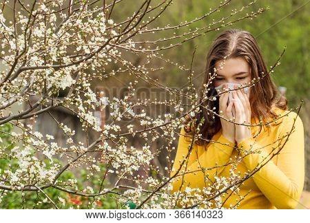 Teen girl with a handkerchief sneezes near a tree. Spring allergy