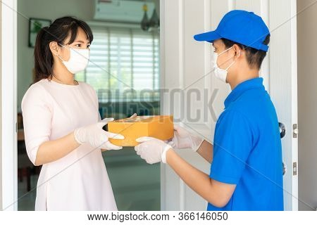 Asian Delivery Man Wearing Face Mask And Glove In Blue Uniform Holding A Cardboard Boxes In Front Ho