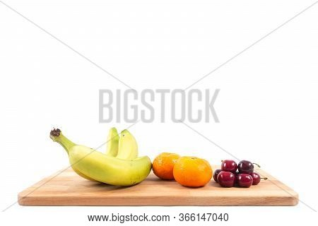 Bananas, Tangerines And Cherries On A White Background. Various Fruits