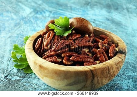 Tasty Pecan Nuts On A Rustic Table.