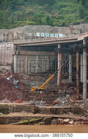Fengdu, Chongqing, China - May 8, 2010: Yangtze River. Crane Works In Rubble On Shoreline Under Tall