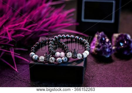 Handmade Bracelets Made Of Natural Stones On A Packing Box. Jewelry, On A Purple Background.