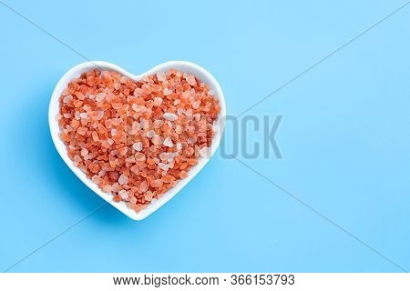 Pink Himalayan Salt In Heart Shape Bowl On Blue Background. Copy Space