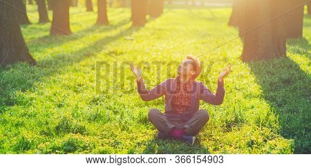 Young Happy Man Sitting On Green Grass In Summer Park, Sunset Nature Outdoor. Look Up On Calm Sun Da