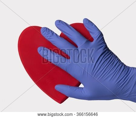 Doctor surgery glove hand touch a heart icon on white background.