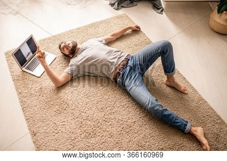 Above view of exhausted young man in jeans lying on carpet in living room and flipping off trainer held online class