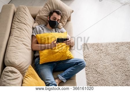 Above view of serious young man in black cloth mask lying on sofa and playing video game on smartphone in quarantine