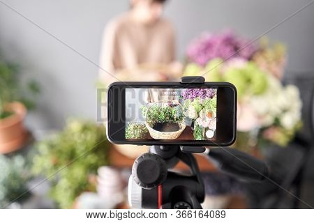 A Woman Writes A Video Blog Or Online Course. Flower School Concept. Florist Woman Creates Flower Ar