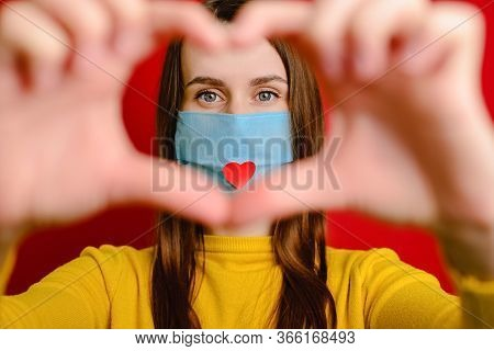 Cute Girl Making Heart Shape Hand Gesture Looking At Camera, Wear Medical Mask With A Red Heart On I