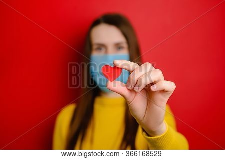 Young Woman In Protective Blue Medical Mask, Isolated On Red Background, Holding Red Heart A Way To