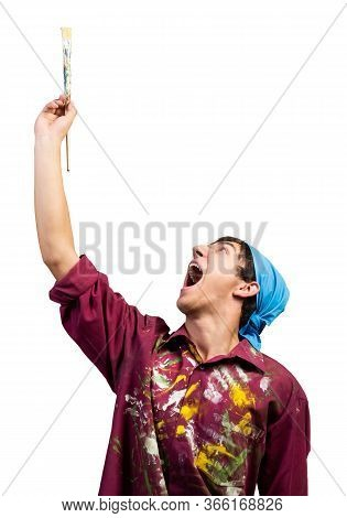 Smiling Young Painter Artist Pointing Upwards With Paintbrush In Hand. Portrait Of Happy Painter Iso