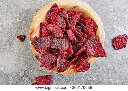 Diet Healthy Eating Concept. Dried Beet Chips Or Baked Beets In A Wooden Bowl, On A Gray Concrete Ba