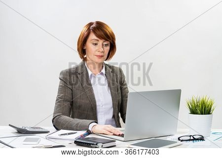 Busy Financial Advisor Working With Computer. Concentrated Accountant Sitting At Desk On White Backg