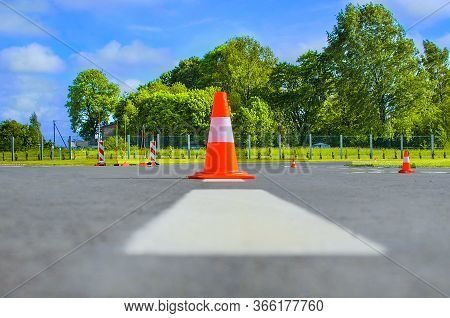 Traffic Cone Standing On Dark Asphalt. Red Rubber Cone In Road Construction. Road Works, Parking Are