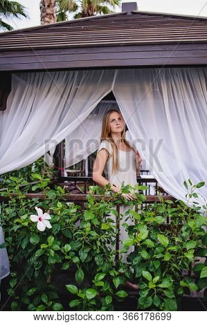 Beautiful Young Slender Long-haired Blond Girl In Gazebo. Nature. Flowers. Wooden Installations Recr