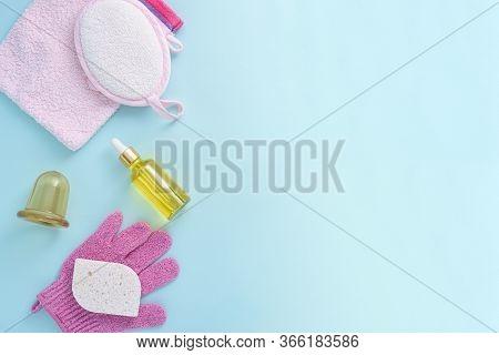 Top View Shower Accessories, Washcloth, Sponge, Serum, Oil, Vacuum Massager On Blue Background, Spa