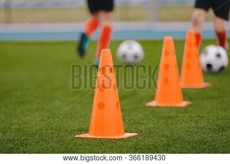 Sports Training Cones On Soccer Pitch. Players Practice Dribbling And Passing Skills On The Grass Fi