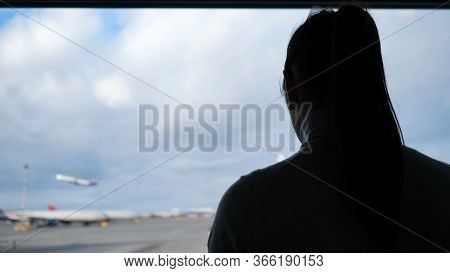 Girl Silhouette With Ponytail In Sweater Looks At Taking Off Plane On Airfield Outside Airport Termi