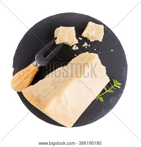 Piece Of Parmesan Cheese On Black Slate Board  Isolated On White. Parmigiano Reggiano, Hard Mature C