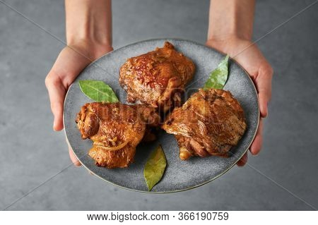 Filipino Chicken Adobo On Gray Plate In Female Hands. Chicken Adobo Is Filipino Cuisine Dish Of Brai