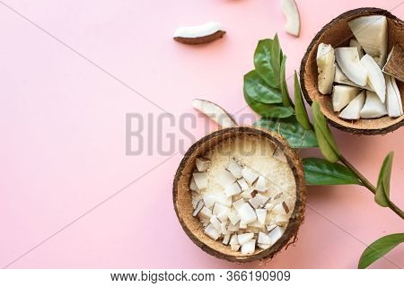 Coconut Cut Into Pieces, Coconut Shavings, A Branch Of Green Leaves Lies On A Pink Background. View