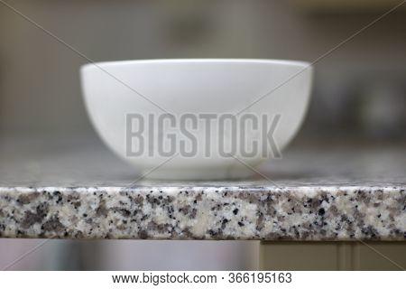 White Ceramic Bowl Standing On Grey Mottled Granite Work Top