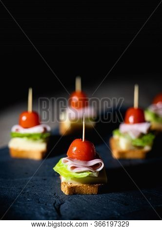 Fresh Appetizers With Toast, Lettuce, Ham And Cherry Tomato On A Stone Board