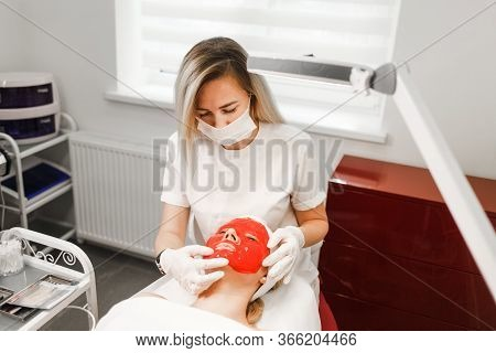 Cosmetologist Applies A Nourishing Mask To The Patient's Face