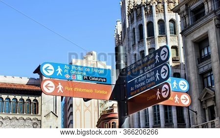 Barcelona, Catalonia, Spain - April 14, 2015: a signpost with information arrows for city guests and tourists in Barcelona street.