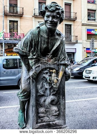 Barcelona, Catalonia, Spain - April 15, 2015: Font del Trinxa - a drinking water fountain in Barcelona by Josep Campeny. Bronze statue of a boy sitting on a fountain.