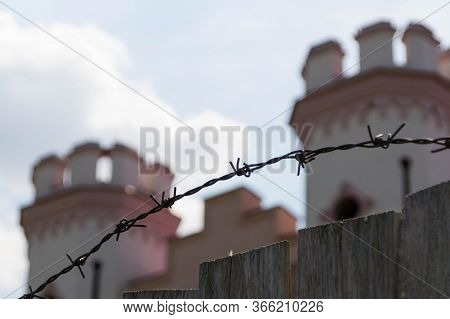 A Wooden Fence And Barbed Wire Enclose An Ancient Palace In The Medieval Gothic Style, Which Is Unde