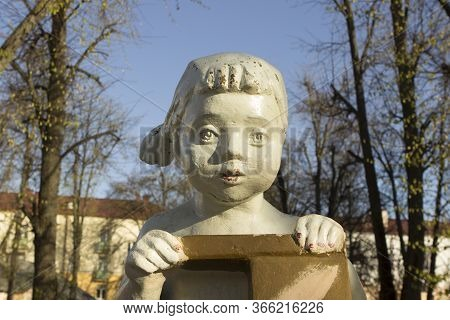 Sculpture Of A Little Girl Of A Child Of Soviet Times In The Courtyard Of An Apartment Building. Min