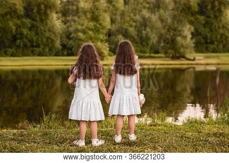 Back View Of Unrecognizable Girls In Similar White Dresses Holding Hands And Admiring Calm Lake Whil
