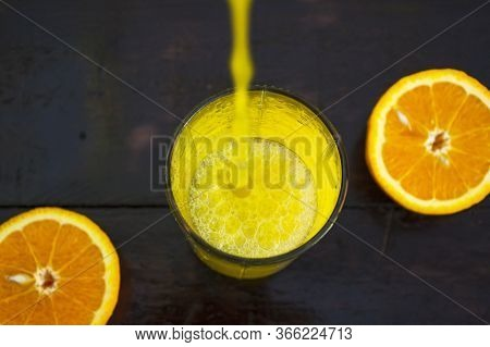 Orange Juice Is Poured Into A Glass On A Wooden Background. Orange Cut In Half, Lies On The Table.