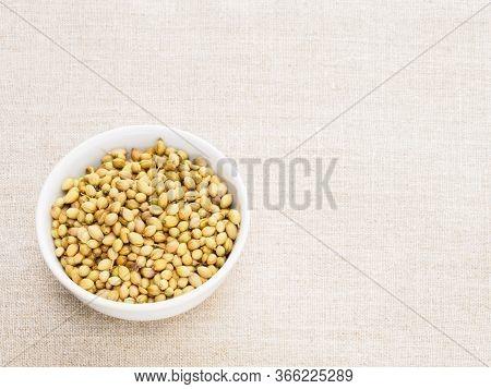 Spice Coriander (coriandrum Sativum) Seeds In Ceramic Bowl On Beige Fabric Background. Indian Cuisin