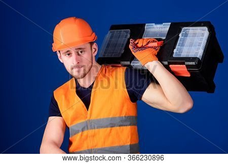 Worker, Repairer, Repairman, Strong Builder On Calm Face Carries Toolbox On Shoulder, Ready To Work.