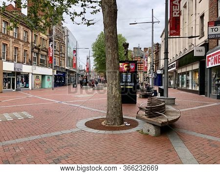 READING, UK - MAY 3, 2020: A few pedestrians pass high street shops on Broad Street closed during the Coronavirus pandemic in Reading, Berkshire, UK.