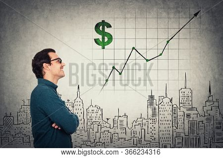 Cheerful Businessman Looking Optimistic At Growing Graph. Business Analyst Wearing Eyeglasses Makes
