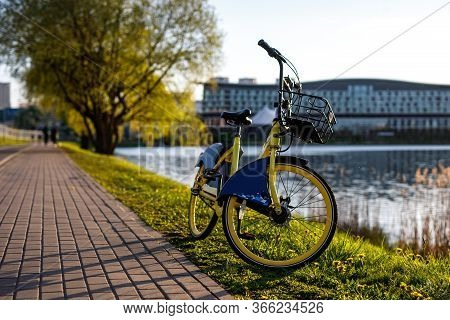 Yellow Rental Bike In The City. Sunset Near The Pond.