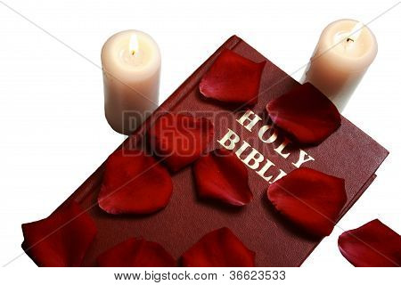 Bible with candles and petals on isolated white